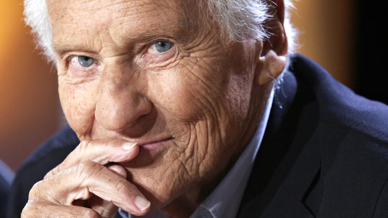 Un vieil homme sourit discrètement, un doigt posé sur ses lèvres.
