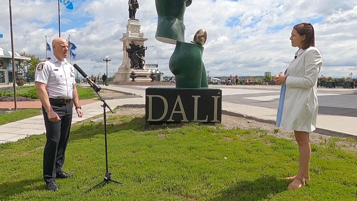 Un policier à gauche, devant un micro, en entrevue avec une journaliste, à droite. Ils sont dehors, on reconnaît une oeuvre de Dali à l'arrière.