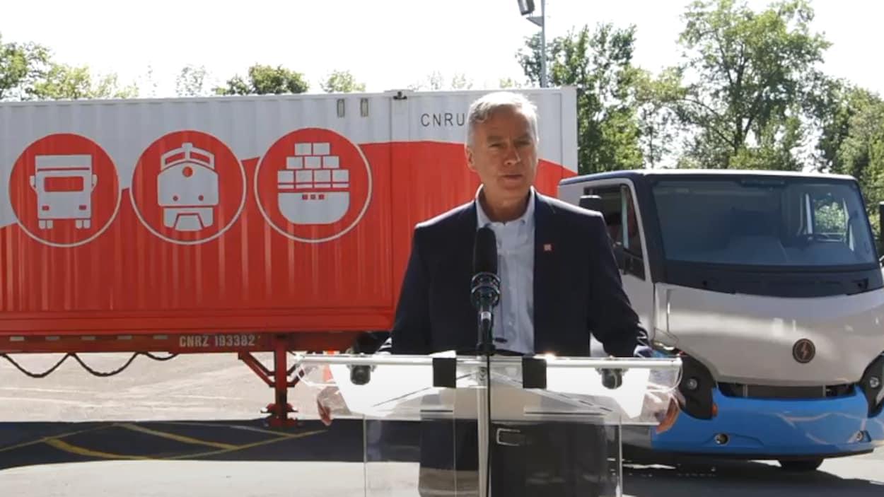 M. Ruest parle au micro devant un camion d'Électrique Lion à l'effigie du CN.