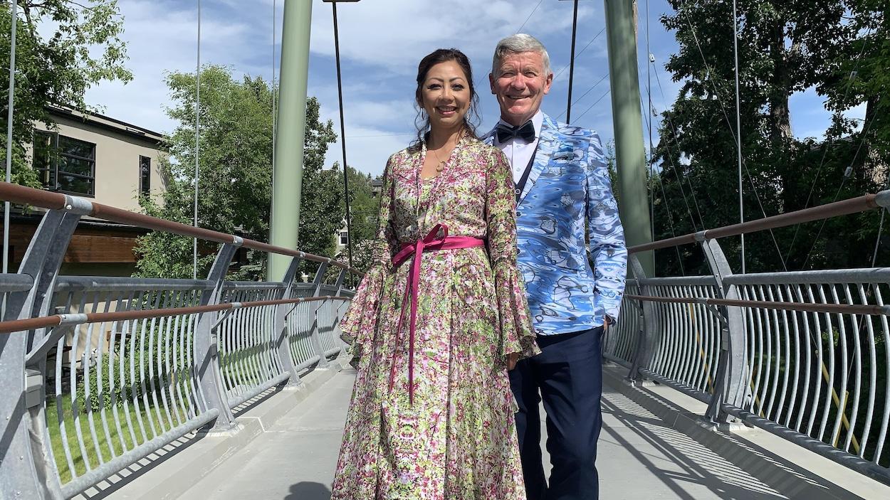 Une femme et un homme posent à l'entrée d'un pont piétonnier.