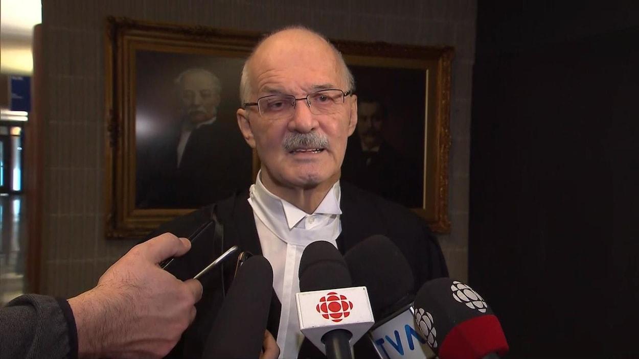 Jean-Pierre Ménard répond aux questions des journalistes au palais de justice de Montréal.