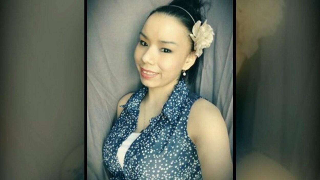 Une jeune femme avec une fleur dans les cheveux.