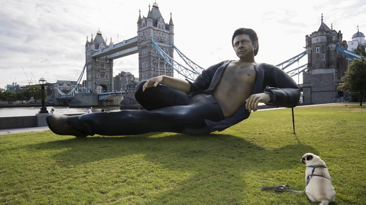 On voit la statue représentant Jeff Goldblum dans  Le parc jurassique , avec à côté un chien et en arrière fond le Tower Bridge.
