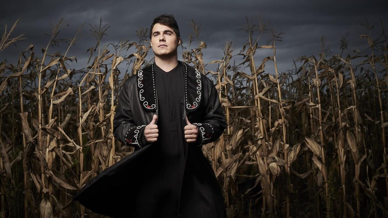 Un homme se tient debout, en costume traditionnel noir brodé, dans un champ de maïs.