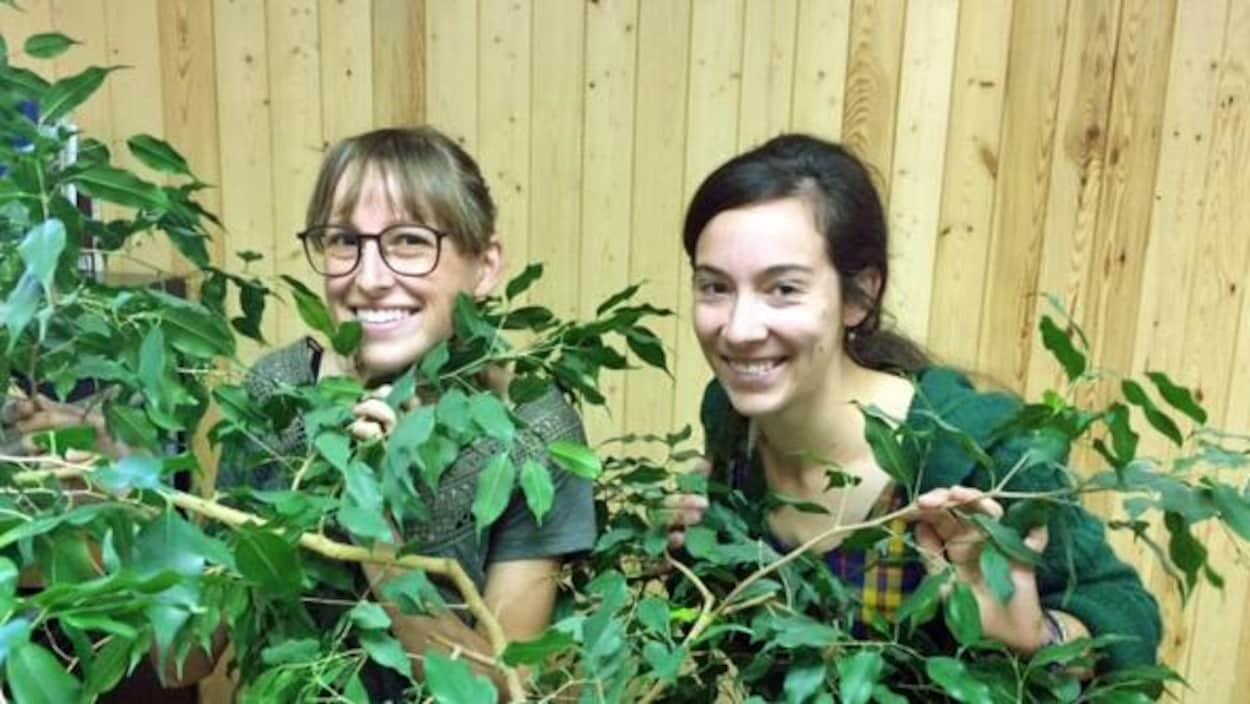 Deux jeunes femmes sourient à la caméra, cachées derrière un petit arbre.