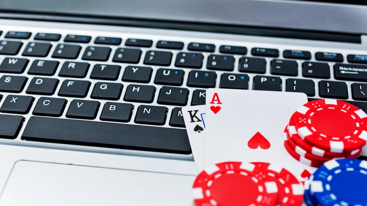 Des jetons de pokers et des cartes sont posés sur un clavier d'ordinateur.