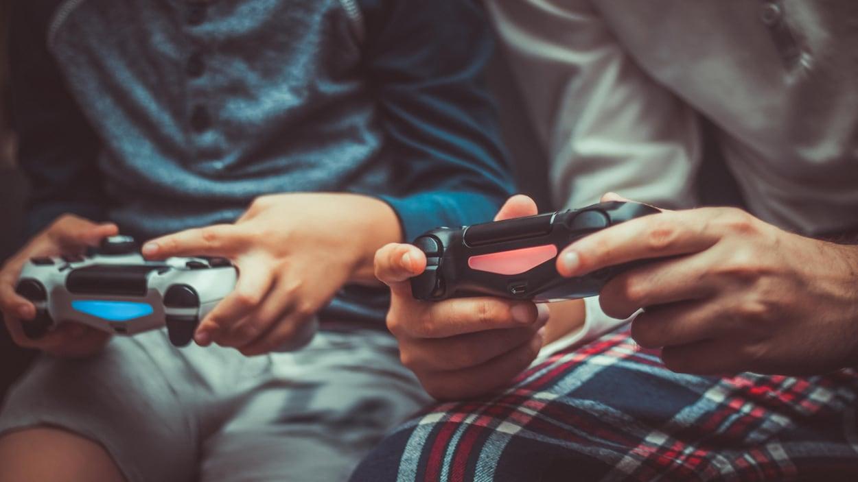 Un jeune et un moins jeune jouent ensemble à un jeu vidéo.