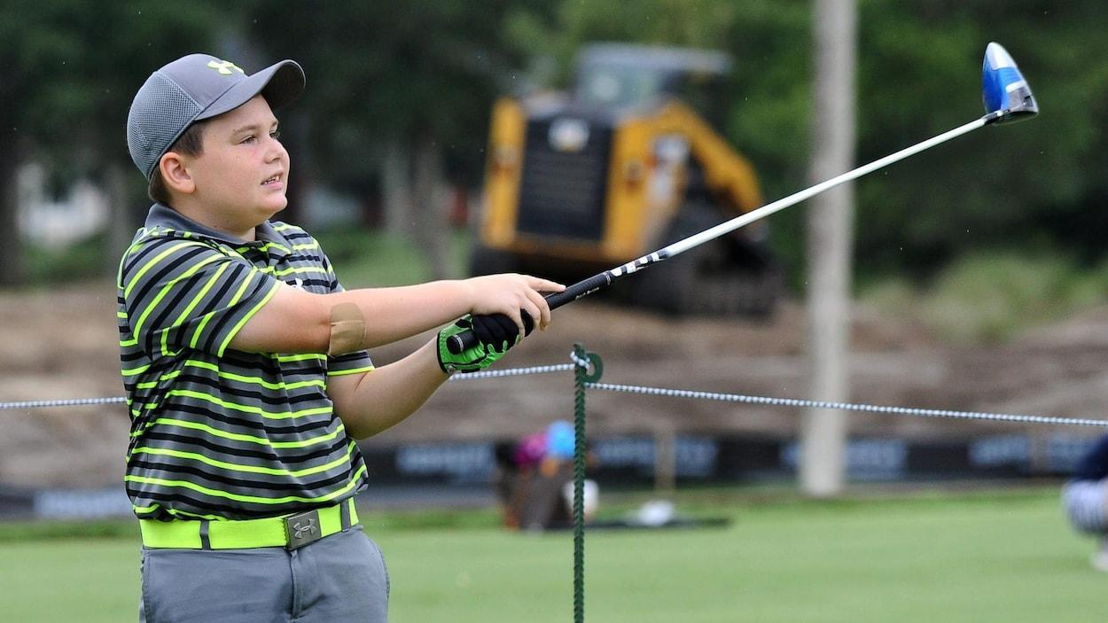 Un jeune golfeur effectue un coup de départ.
