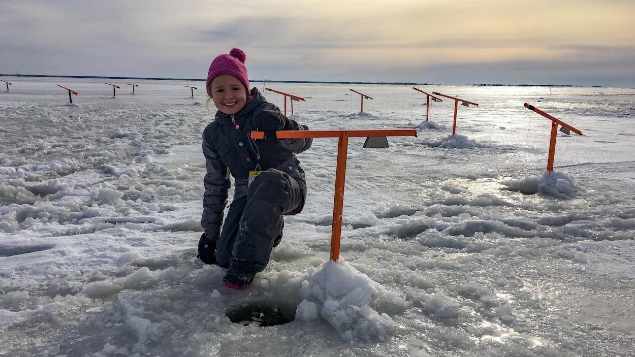 Une jeune pêcheuse surveille ses lignes de pêche blanche sur la glace du lac Saint-Pierre.