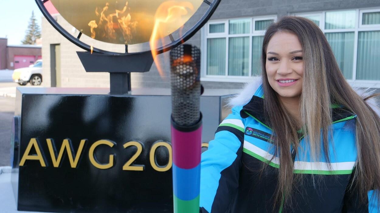 Une jeune femme porte le flambeau des Jeux d'hiver de l'Arctique.