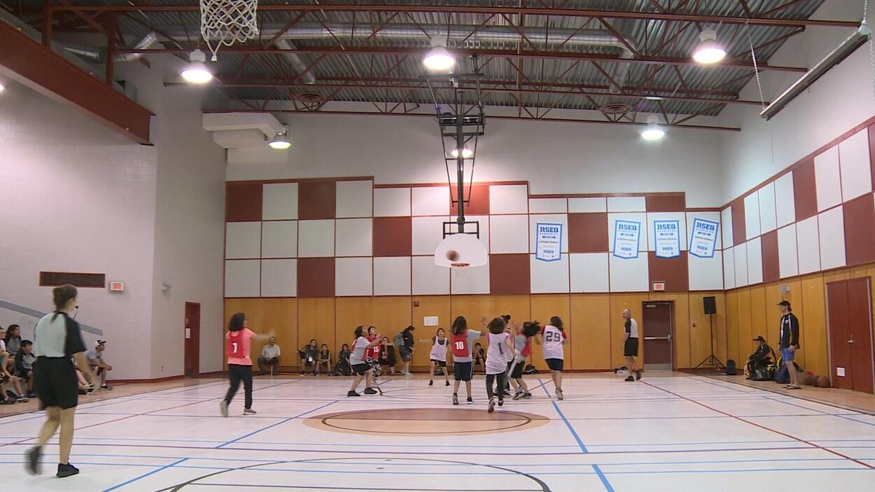 Des jeunes avec des dossards jouent au basketball dans un gymnase.