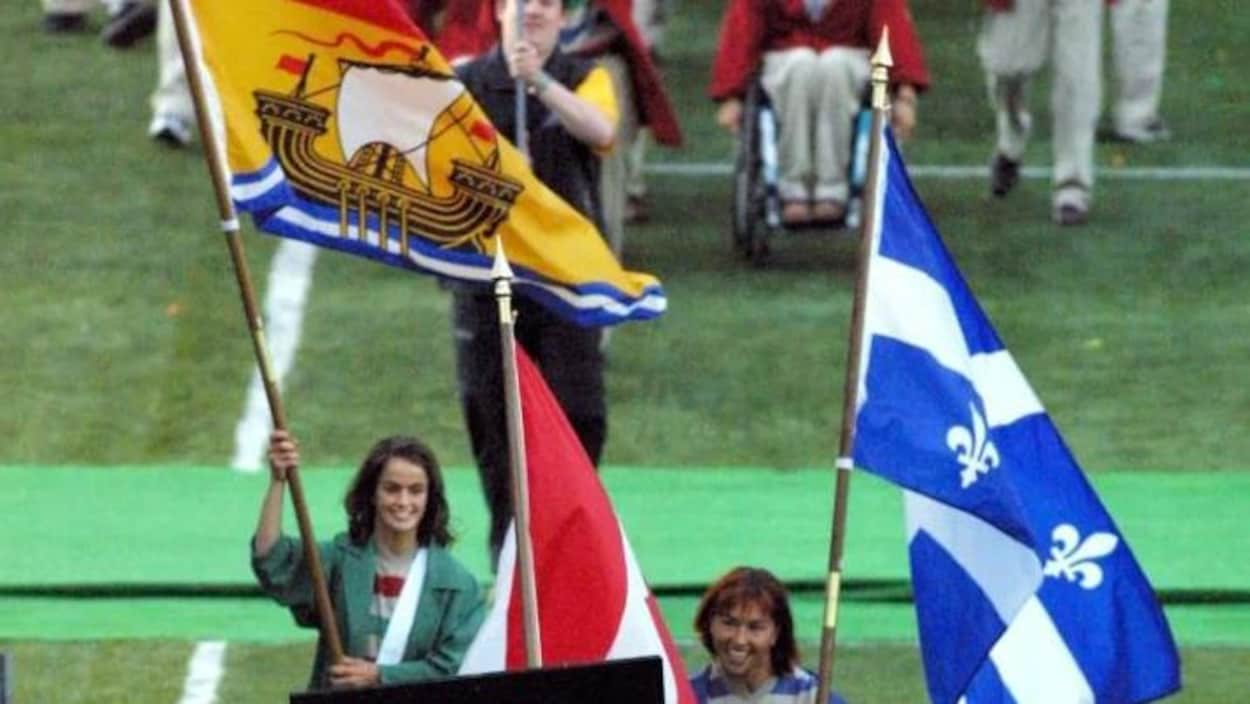 Les porte-drapeaux du Nouveau-Brunswick, du Canada et du Québec précèdent les athlètes et artistes.