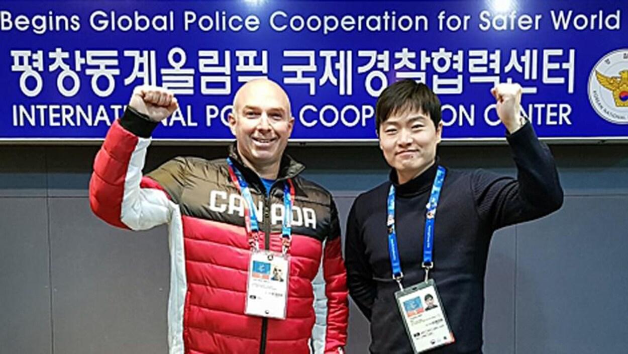 Un homme blanc, qui porte un manteau d'hiver avec la mention Canada, et un homme asiatique lèvent tous les deux un bras en l'air, le poing serré, en signe de victoire. Ils portent tous les deux une pièce d'identification au cou et sont debout devant une pancarte avec des caractères coréens.
