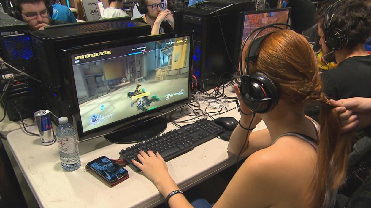 Une adolescente joue à un jeu vidéo sur un ordinateur.