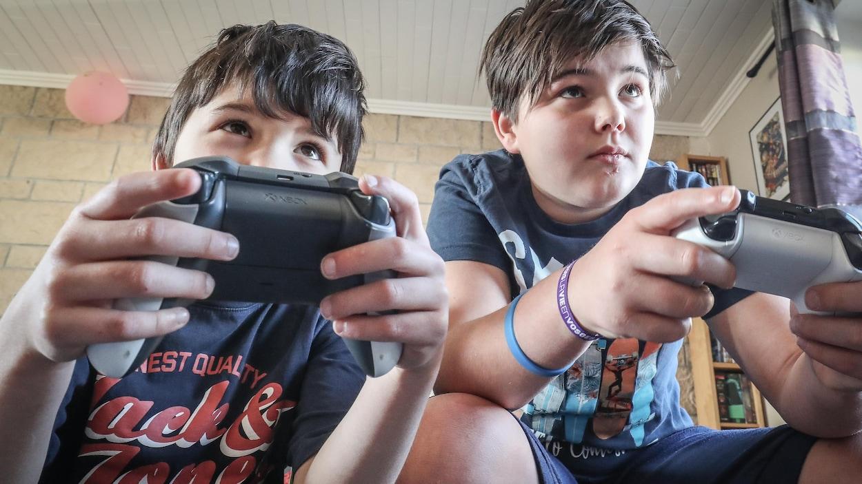 Deux jeunes garçons regardent devant eux en tenant des manettes de jeux vidéo.