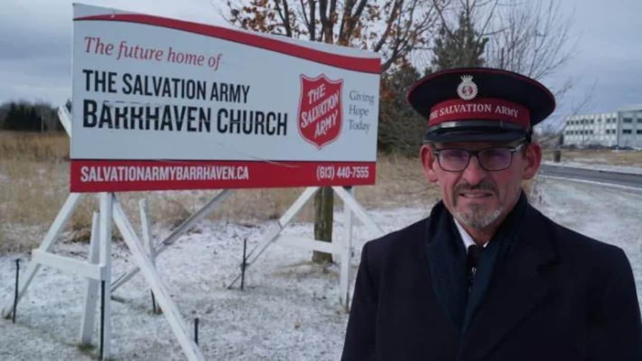 Un homme en uniforme devant une pancarte de l'Armée du Salut dehors l'hiver