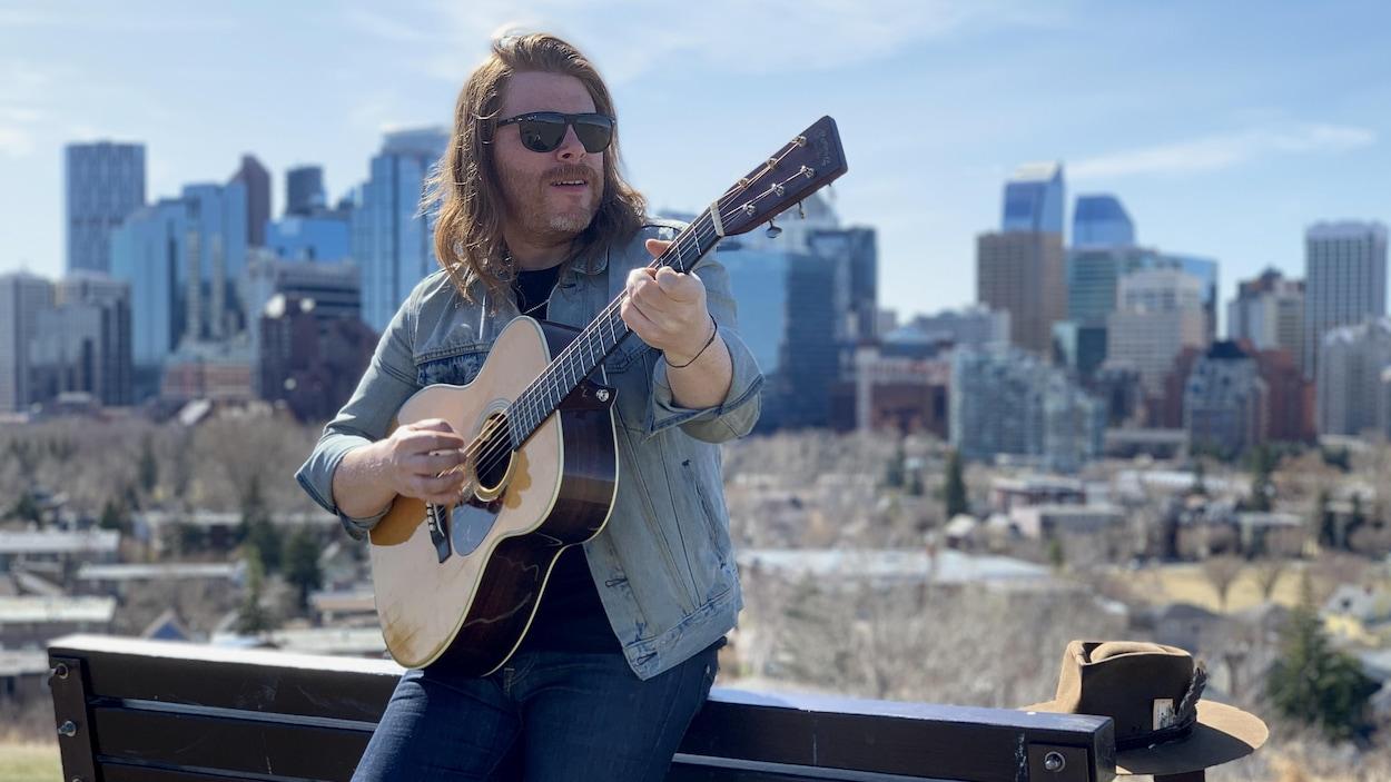 Un homme appuyé sur un banc tient joue de la guitare.
