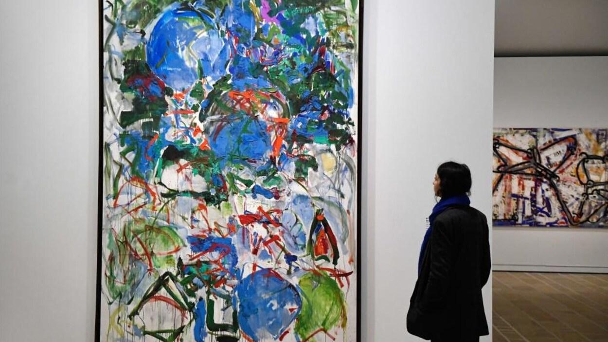 Une femme regarde une toile colorée.