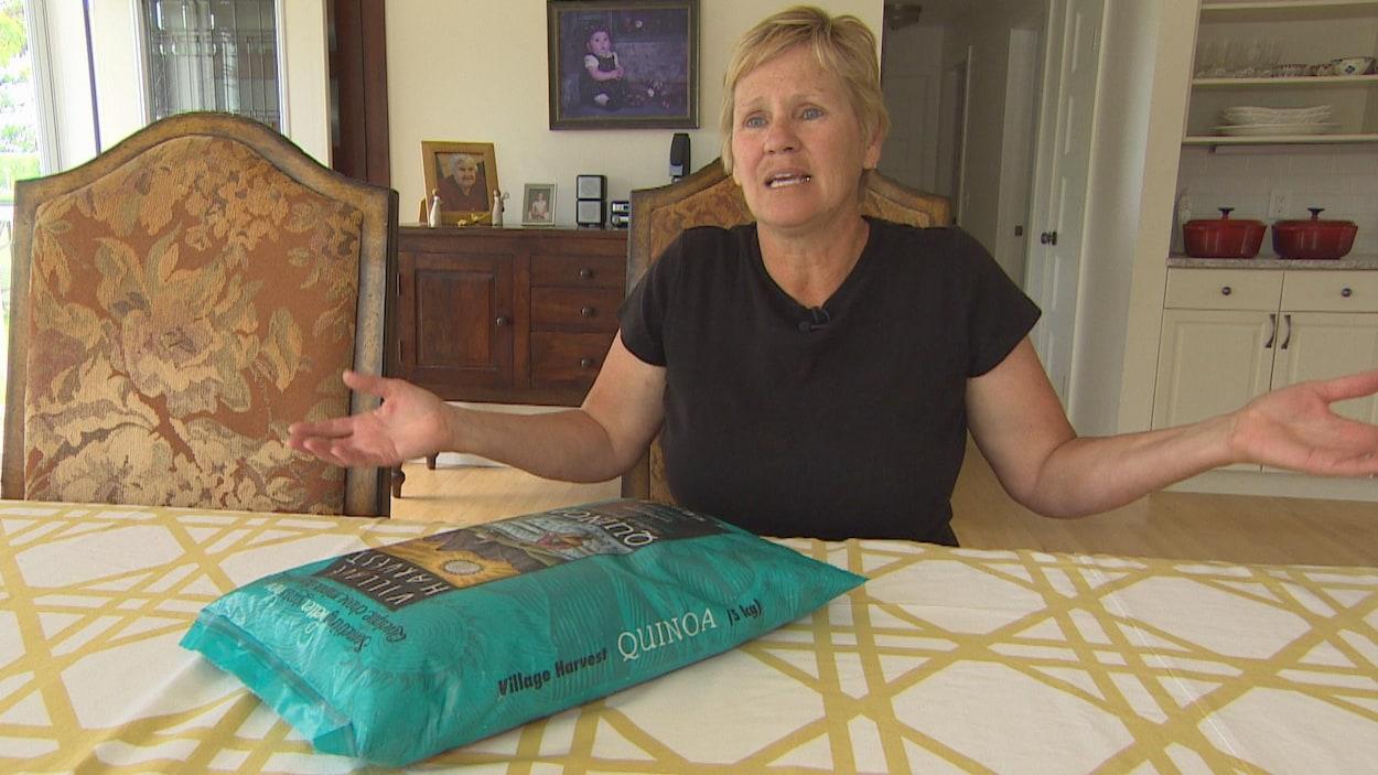 Une dame d'une cinquantaine d'années, avec des cheveux blonds coupés courts, lève les mains en signe d'impuissance devant un grand sac de quinoa posé sur sa table à manger.