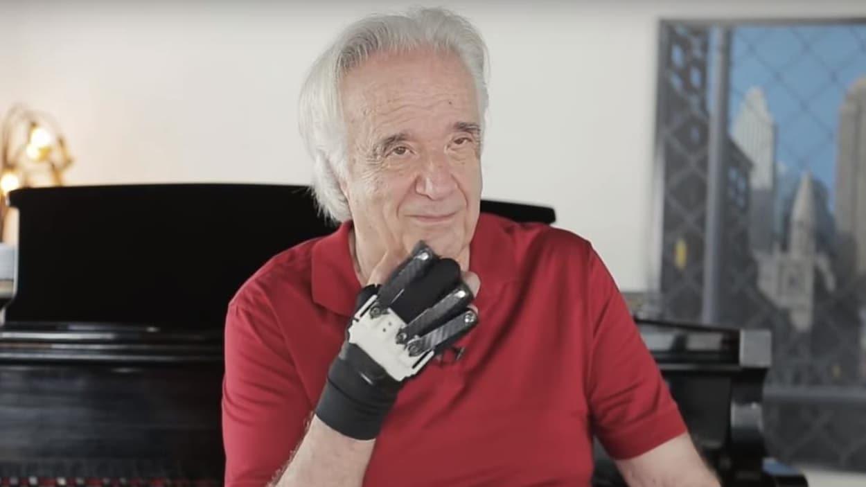 Un homme âgé ayant portant un gant métallique est assis devant un piano.