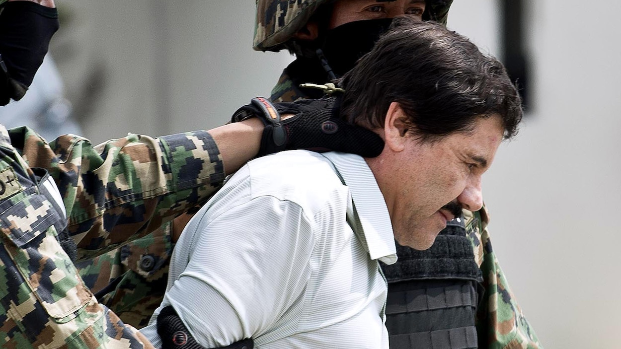 Deux soldats flanquent Joaquin « El Chapo » Guzman qui apparaît en chemise blanche, la tête légèrement penchée vers le bas.