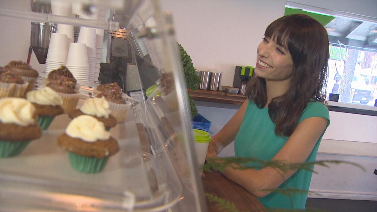 Jodie Emery devant une vitrine de cupcakes.