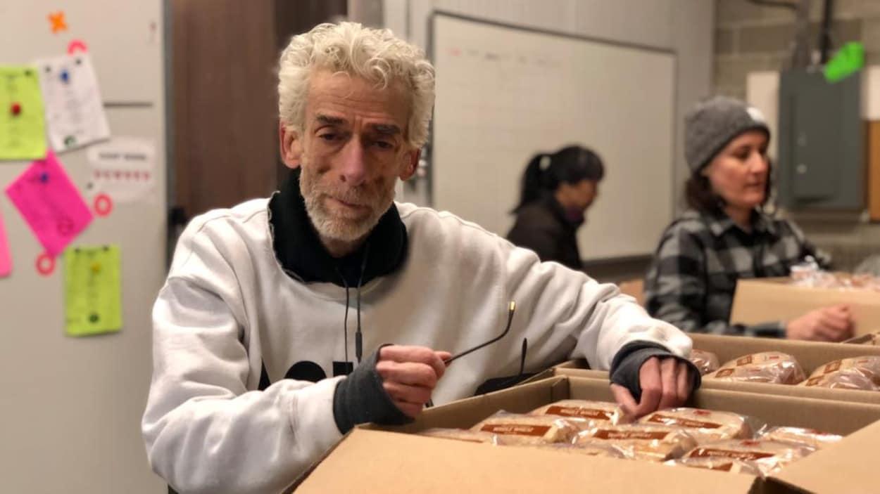 Un homme s'appui sur une boîte de nourriture.