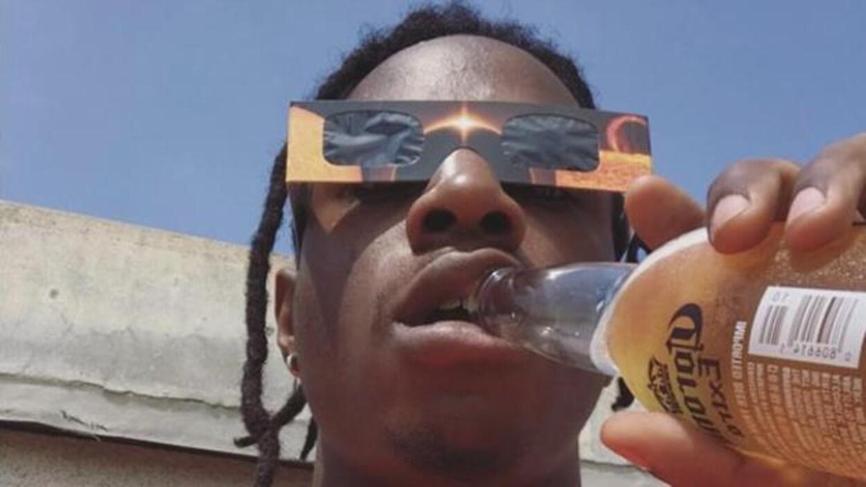 Le rappeur Joey Bada$$ portant des lunettes protectrices pendant l'éclipse du 21 août.