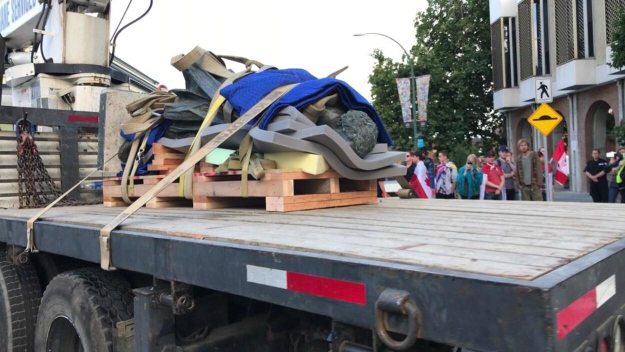 La statue de John A. Macdonald est enveloppée d'un tapis en polystyrène et allongée sur la remorque d'un camion à Victoria