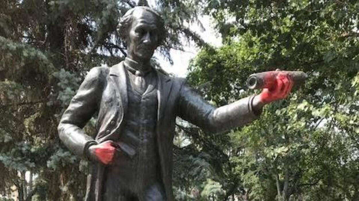 Statue de John A. Macdonald au centre-ville de Regina, dont les mains sont recouvertes de peinture rouge.