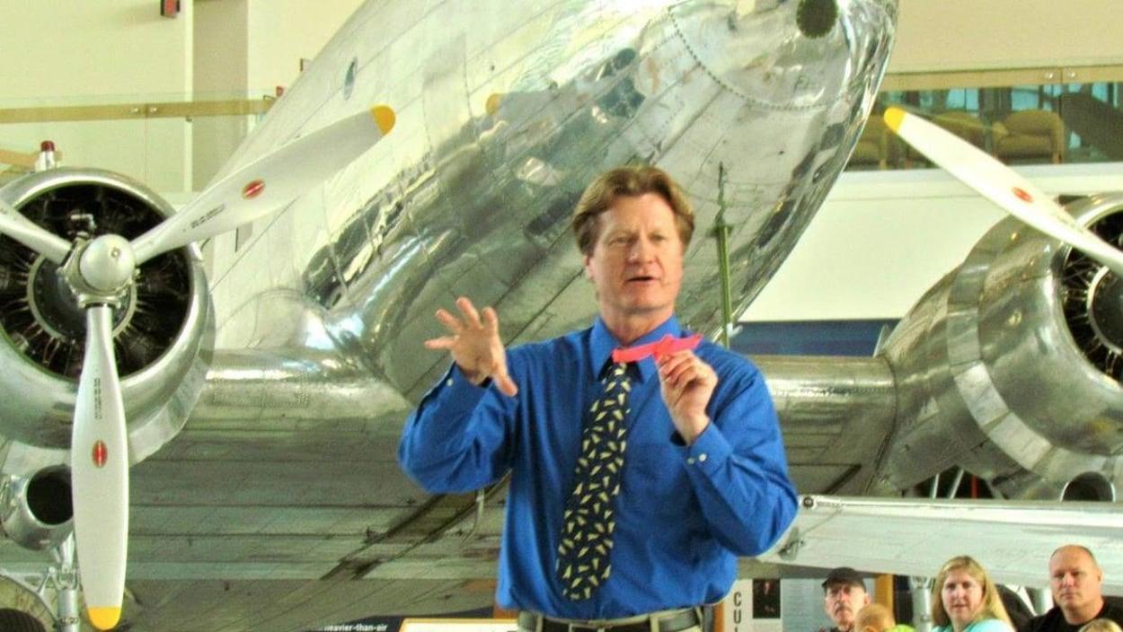 Une homme lance un avion en papier devant un avion réel. Des adultes et des enfants le regardent.