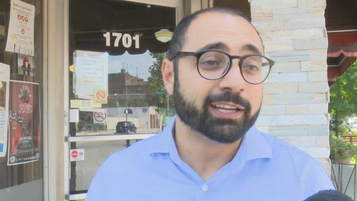 Un homme avec des lunettes et une barbe devant un magasin répond à un journaliste