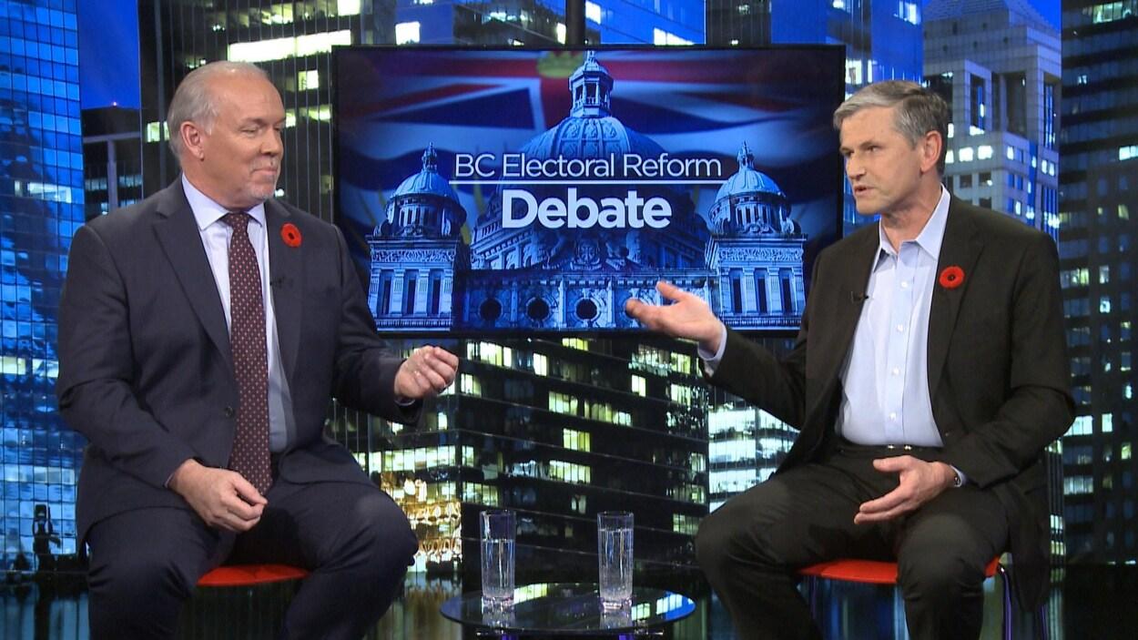 John Horgan et Andrew Wilkinson assis devant un écran de télé où il est écrit en anglais, la réforme électorale de la Colombie-Britannique, débat.