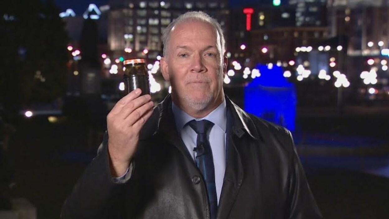 Le chef du Nouveau Parti démocratique de la Colombie-Britannique, John Horgan, tient un bocal rempli de bitume.