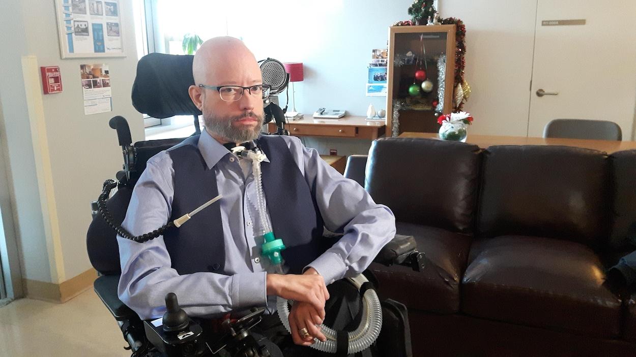 Jonathan Marchand assis dans son fauteuil roulant électrique avec son respirateur artificiel.