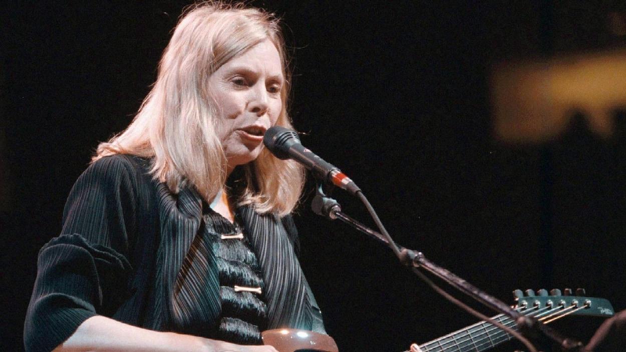 Joni Mitchell chante avec une guitare sur scène.