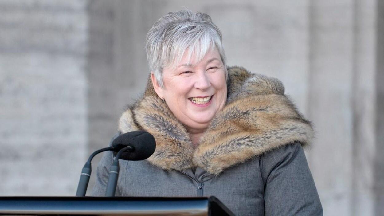 Bernadette Jordan, souriante, parle dans un micro installé devant l'édifice.