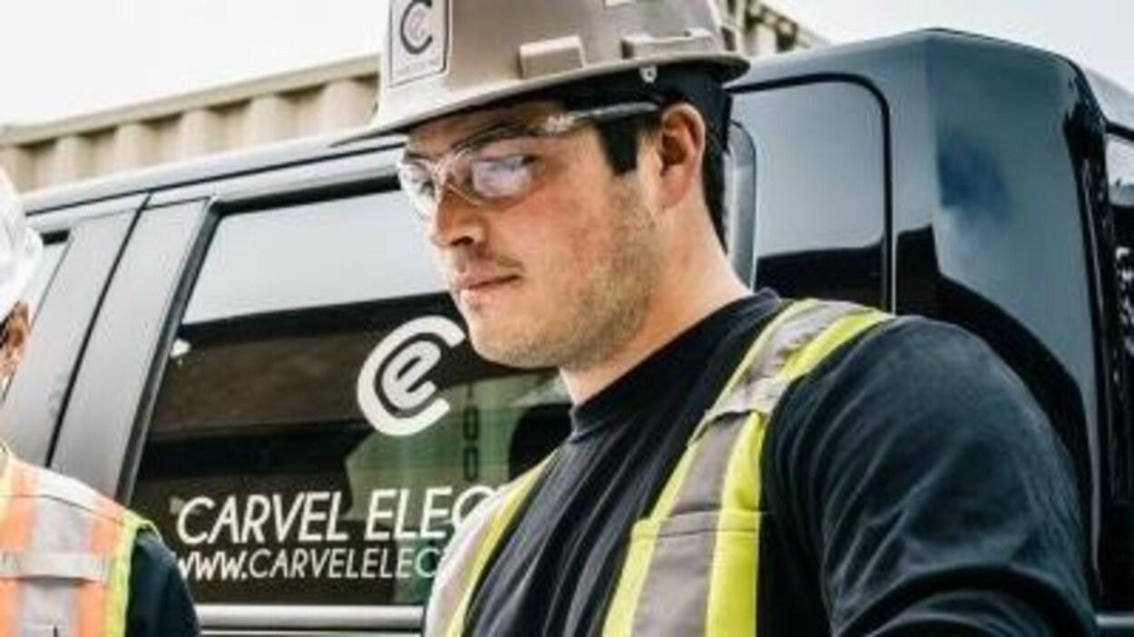Un jeune homme portant un casque et des lunettes de protection est debout devant un camion.