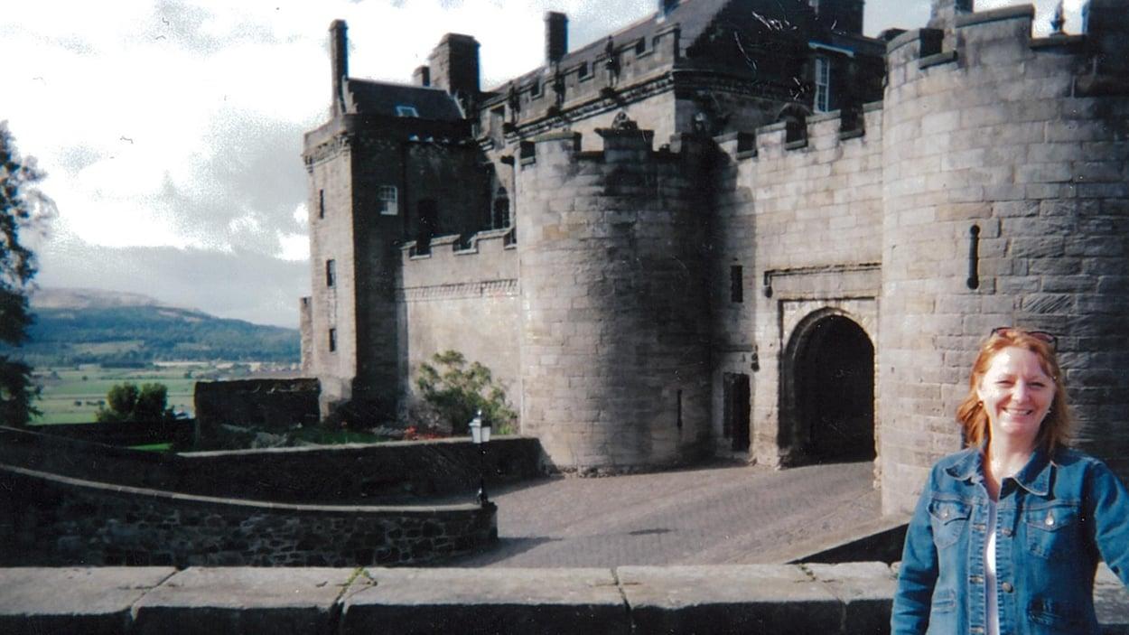Une femme pose devant un château médiéval.