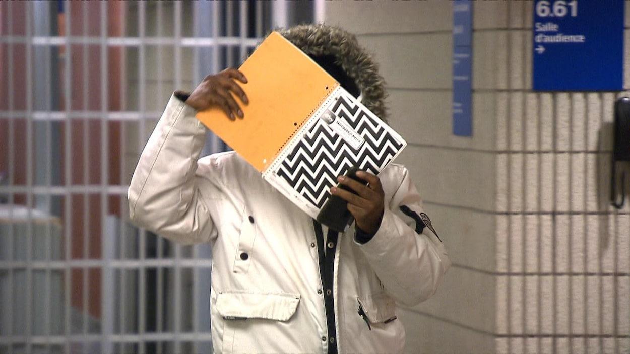 Un homme tient un cahier devant son visage dans un couloir de palais de justice.