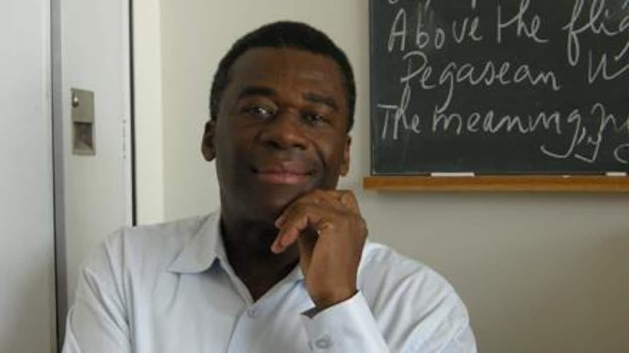 Portrait du poète d'origine haïtienne Joubert Satyre assis à un bureau, une main sous le menton, devant un tableau noir.