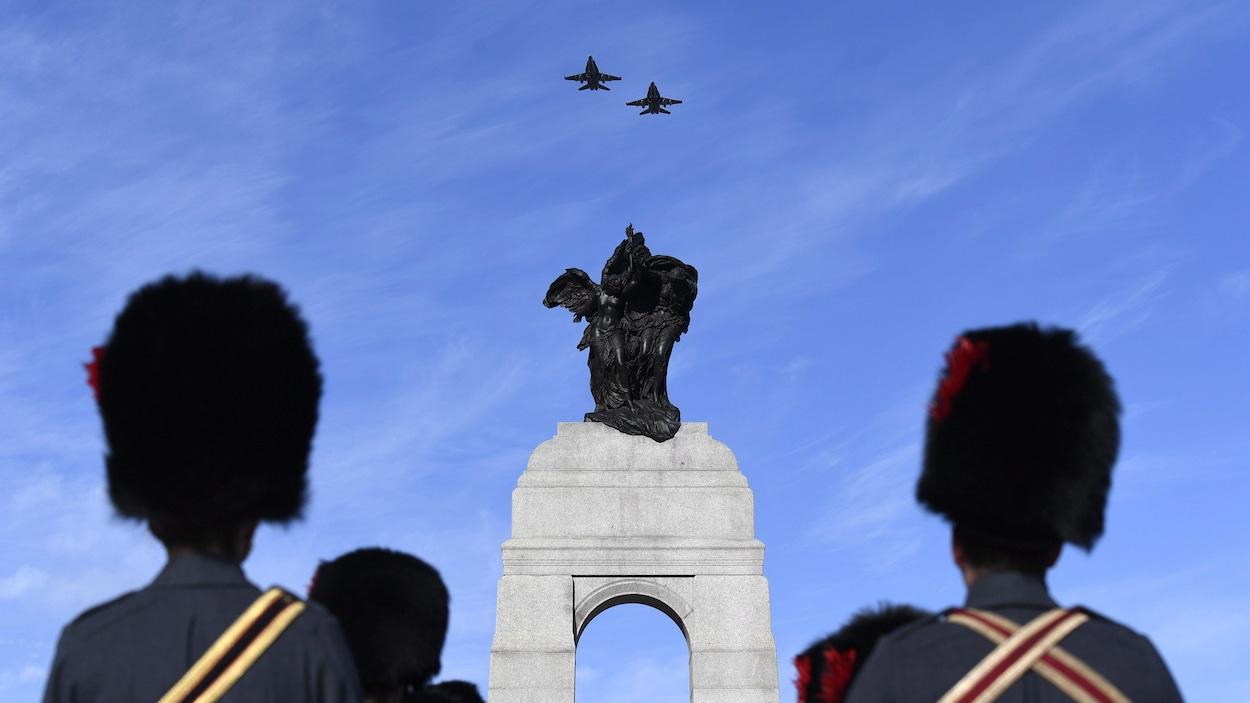 Des militaires en costume d'apparat observent le passage de deux avions CF-18 au-dessus du Monument commémoratif de guerre du Canada.
