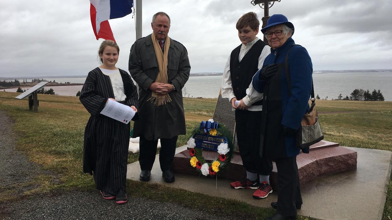 Deux enfants vêtus de costumes traditionnels en compagnie d'un homme et une femme, debout devant un monument commémoratif et un mat où flotte le drapeau acadien