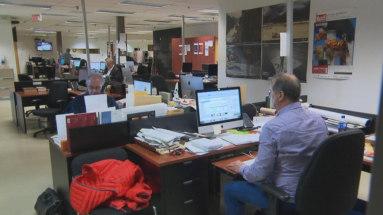 Des journalistes travaillent dans la salle des nouvelles du journal Le Quotidien.