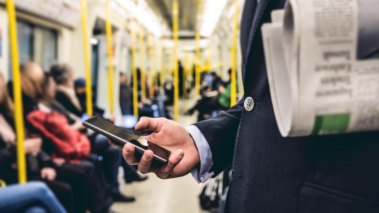 Un homme transportant un journal consulte un téléphone intelligent dans le métro.
