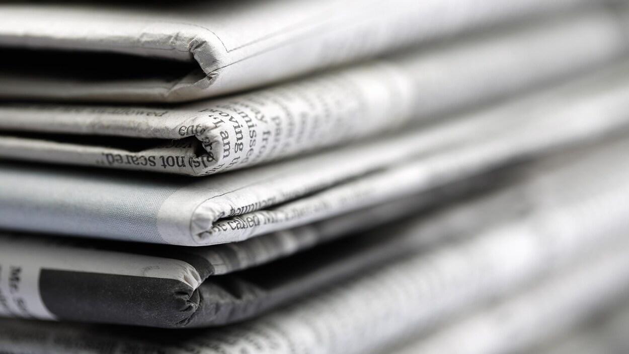 Un gros plan sur une pile de journaux pliés.