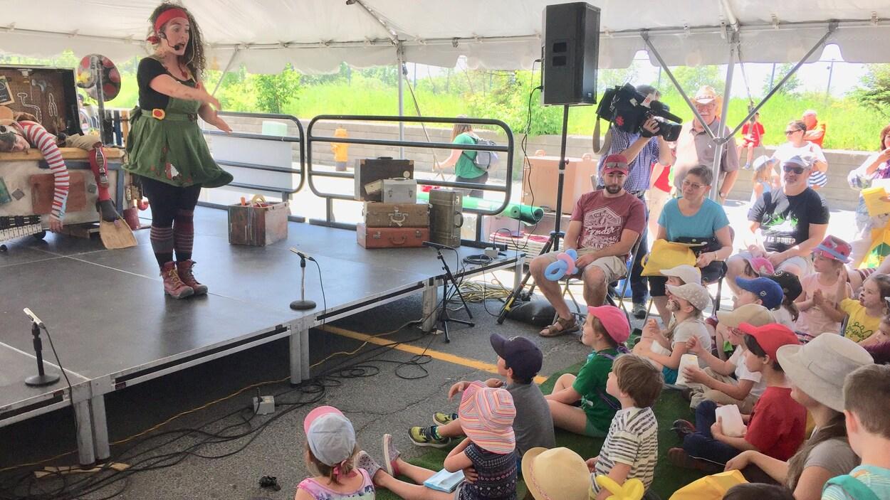 Une femme sur une scène devant beaucoup d'enfants