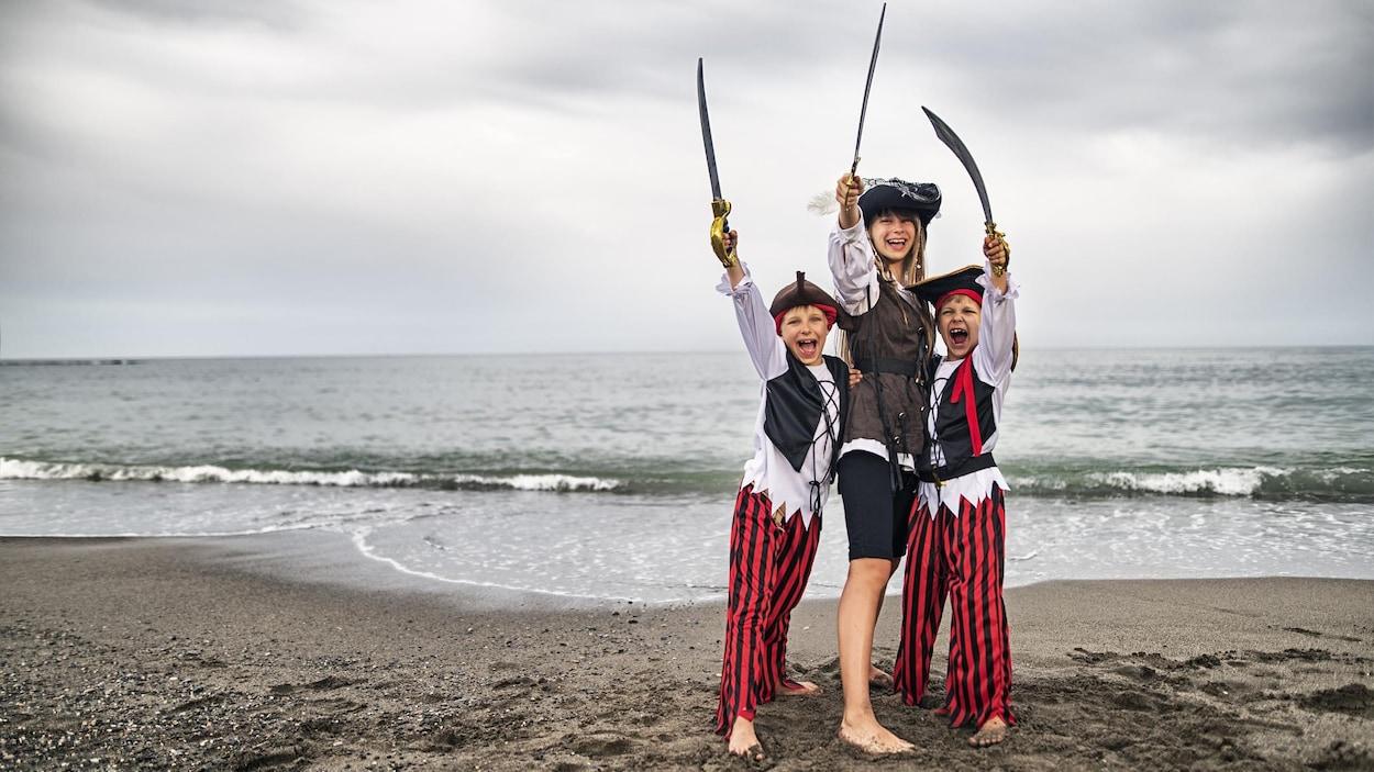 Trois petits pirates, une fille de 11 ans et deux garçons de 7 ans se s'amusent sur la plage.