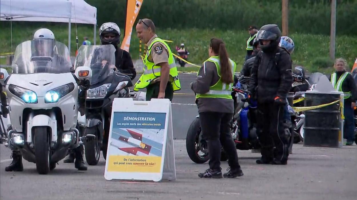 Des motocyclistes et des moniteurs lors d'une démonstration portant sur les angles morts des véhicules lourds.