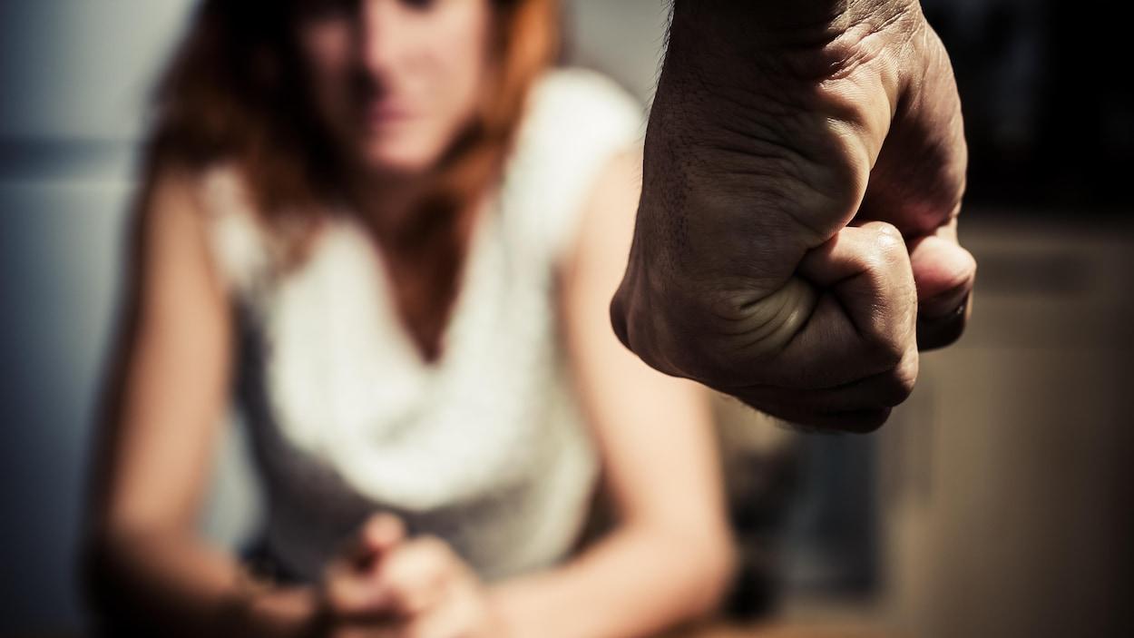 Un poing devant une femme assise.